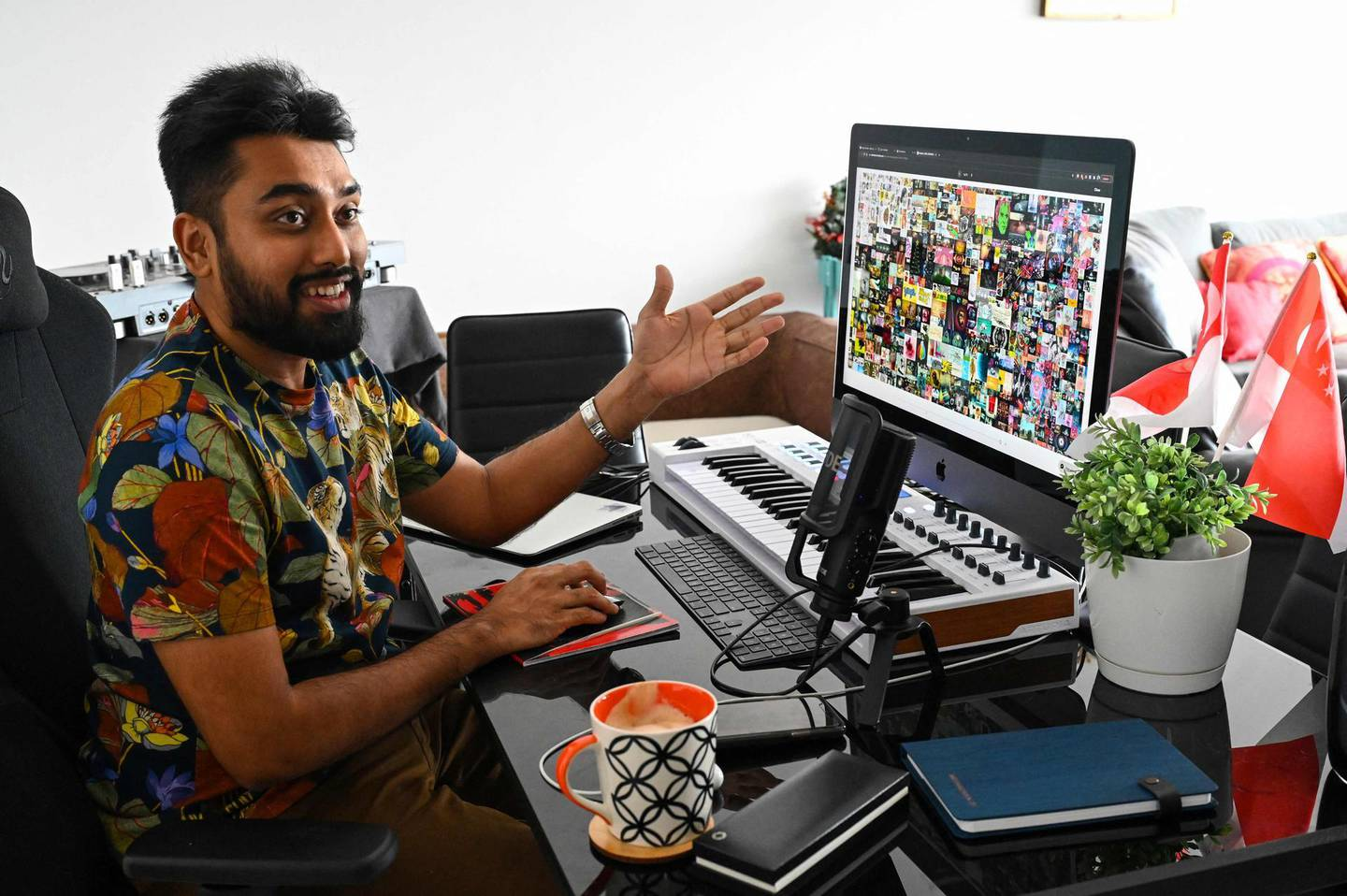 """This picture taken on April 7, 2021 shows blockchain entrepreneur Vignesh Sundaresan, also known by his pseudonym MetaKovan, showing the digital artwork non-fungible token (NFT) """"Everydays: The First 5,000 Days"""" by artist Beeple in his home in Singapore. Last month the programmer bought the world's most expensive NFT for $69.3 million, highlighting how virtual work is establishing itself as a new creative genre. - RESTRICTED TO EDITORIAL USE - MANDATORY MENTION OF THE ARTIST UPON PUBLICATION - TO ILLUSTRATE THE EVENT AS SPECIFIED IN THE CAPTION  TO GO WITH Singapore-US-arts-IT, INTERVIEW by Catherine LAI  / AFP / Roslan RAHMAN / RESTRICTED TO EDITORIAL USE - MANDATORY MENTION OF THE ARTIST UPON PUBLICATION - TO ILLUSTRATE THE EVENT AS SPECIFIED IN THE CAPTION  TO GO WITH Singapore-US-arts-IT, INTERVIEW by Catherine LAI"""