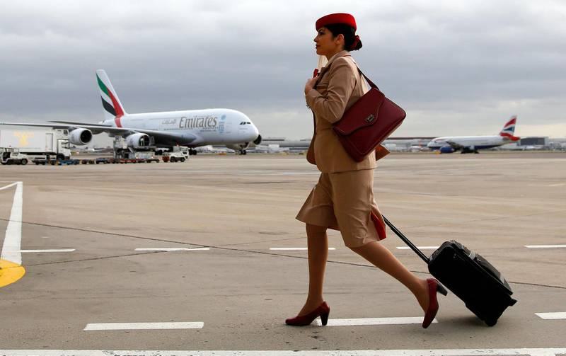 An Emirates air stewardess pulls a luggage case as she walks in the tarmac near one of the airline's Airbus A380 aircraft, at Terminal 3 of Heathrow Airport in London, U.K., on Thursday, Dec. 5, 2013. Emirates, the world's largest buyer of Airbus A380 aircraft, is exploring engine options for a batch of 50 additional superjumbos, handing Rolls-Royce Holdings Plc an opportunity to unseat a General Electric Co. and Pratt & Whitney joint venture that powers the existing jets. Photographer: Paul Thomas/Bloomberg