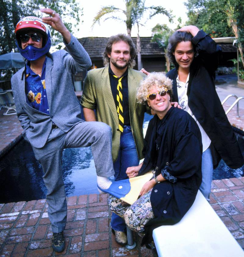 """LOS ANGELES - 1985:  Guitarist Eddie Van Halen (white shirt), bassist Mark Anthony (beard), singer Sammy Hagar (blonde curls) and drummer Alex Van halen (suit, sunglasses) of the rock and roll band """"Van Halen"""" pose for a photo session by the pool at Eddie's house--studio on Coldwater Canyon in circa 1985 in Los Angeles, California. (photo by Ann Summa/Getty Images)"""