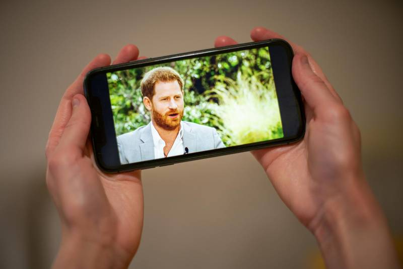 A man watches the Duke and Duchess of Sussex interview with Oprah Winfrey, which is being shown on ITV, on a phone screen in a flat in London. Picture date: Monday March 8, 2021. (Photo by Aaron Chown/PA Images via Getty Images)