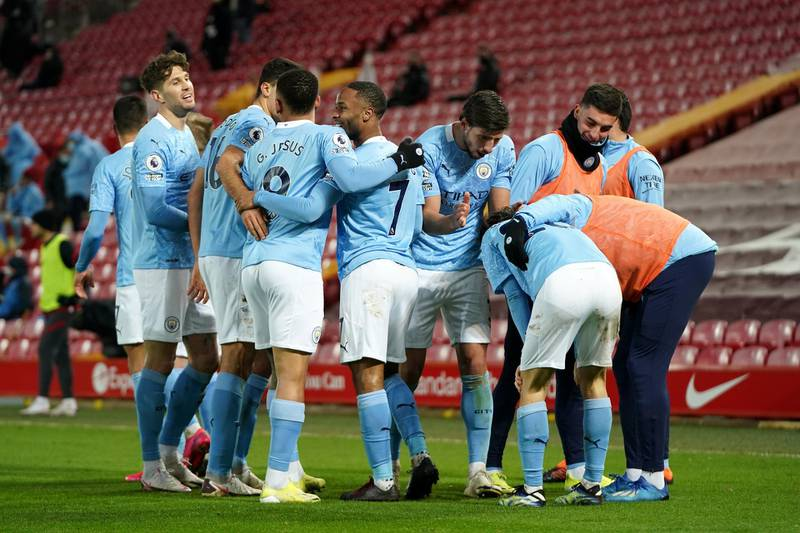 LIVERPOOL, ENGLAND - FEBRUARY 07: Raheem Sterling of Manchester City celebrates with team mates after scoring their side's third goal during the Premier League match between Liverpool and Manchester City at Anfield on February 07, 2021 in Liverpool, England. Sporting stadiums around the UK remain under strict restrictions due to the Coronavirus Pandemic as Government social distancing laws prohibit fans inside venues resulting in games being played behind closed doors (Photo by Jon Super - Pool/Getty Images)