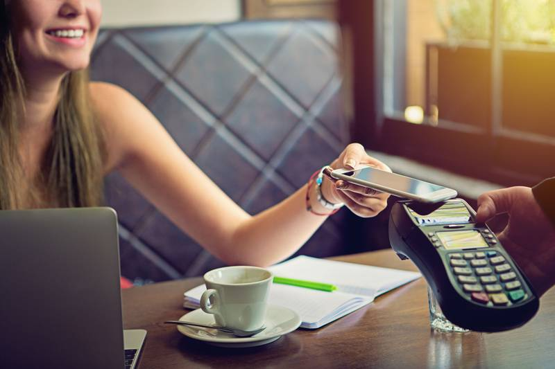 Young woman is paying in the cafe using her mobile phone. Getty Images