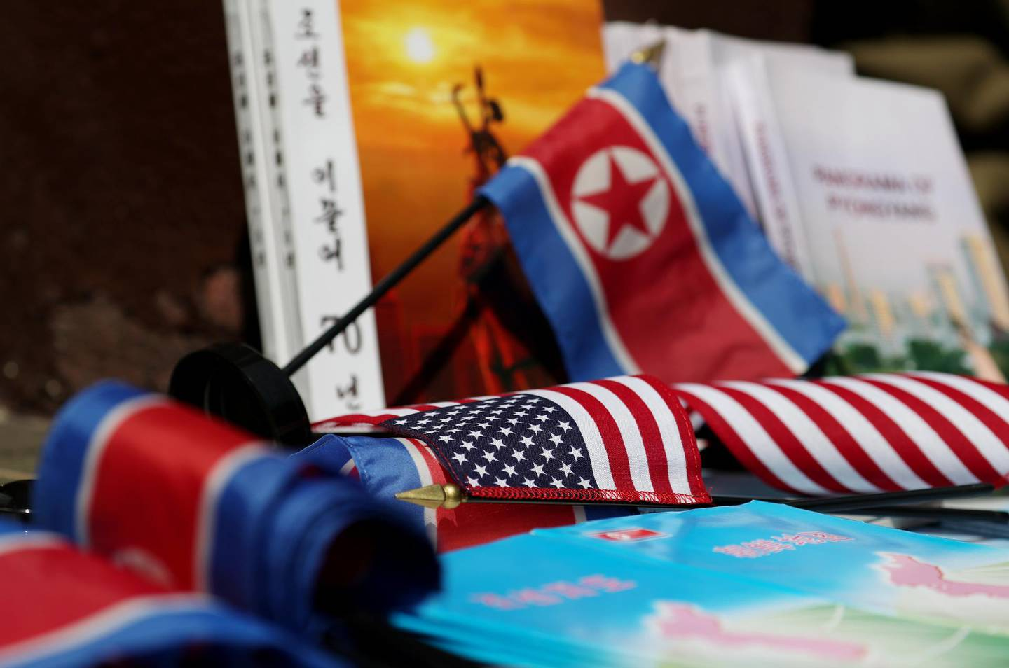 North Korean and American flags and books are displayed for sale at a stall outside the St. Regis hotel, where North Korean leader Kim Jong Un is staying in Singapore, on Monday, June 11, 2018. PresidentDonald Trumpis about to see whether his bet on North Korea will pay off: thatKimJong Un's desire to end his country's economic strangulation and pariah status will prevail over the dictator's fear of relinquishing his nuclear threat. Photographer: SeongJoon Cho/Bloomberg
