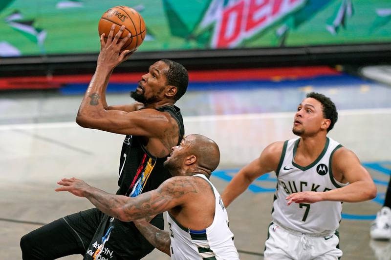 Brooklyn Nets forward Kevin Durant (7) goes up to shoot with Milwaukee Bucks forward P.J. Tucker (17) and guard Bryn Forbes (7) looking on during the third quarter of Game 2 of an NBA basketball second-round playoff series, Monday, June 7, 2021, in New York. (AP Photo/Kathy Willens)