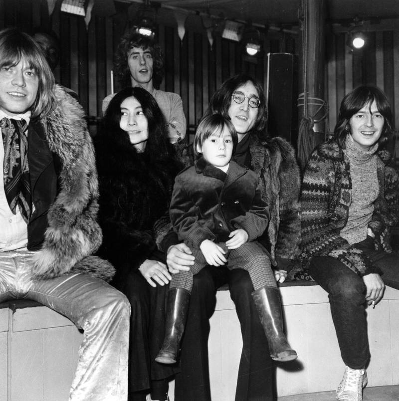 L-R: Rolling Stones guitarist Brian Jones, artist Yoko Ono and her husband, Beatles guitarist John Lennon, with his son Julian on his lap, guitarist Eric Clapton, and behind them singer Roger Daltrey of The Who, gather at Internel Studios in Stonebridge Park, Wembley, where they watched some of the circus acts who will appear in a television spectacular planned by the Rolling Stones, 'The Rolling Stones' Rock 'n' Roll Circus,' England, December 10, 1968. (Photo by Hulton Archive/Getty Images)
