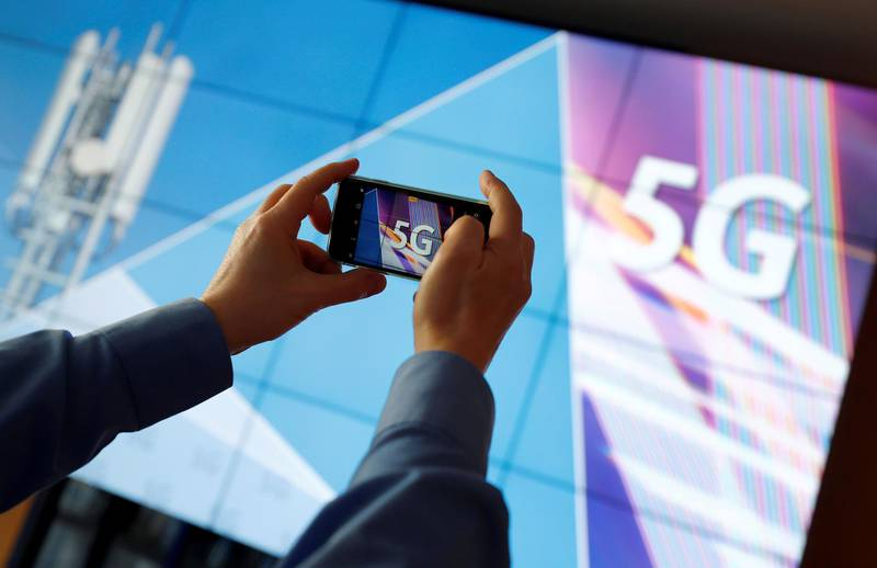 FILE PHOTO: FILE PHOTO: A journalist uses his mobile phone to take a picture of the 5G logo prior to the auction of spectrum for 5G services at the Bundesnetzagentur head quarters in Mainz, Germany, March 19, 2019.  REUTERS/Kai Pfaffenbach/File Photo