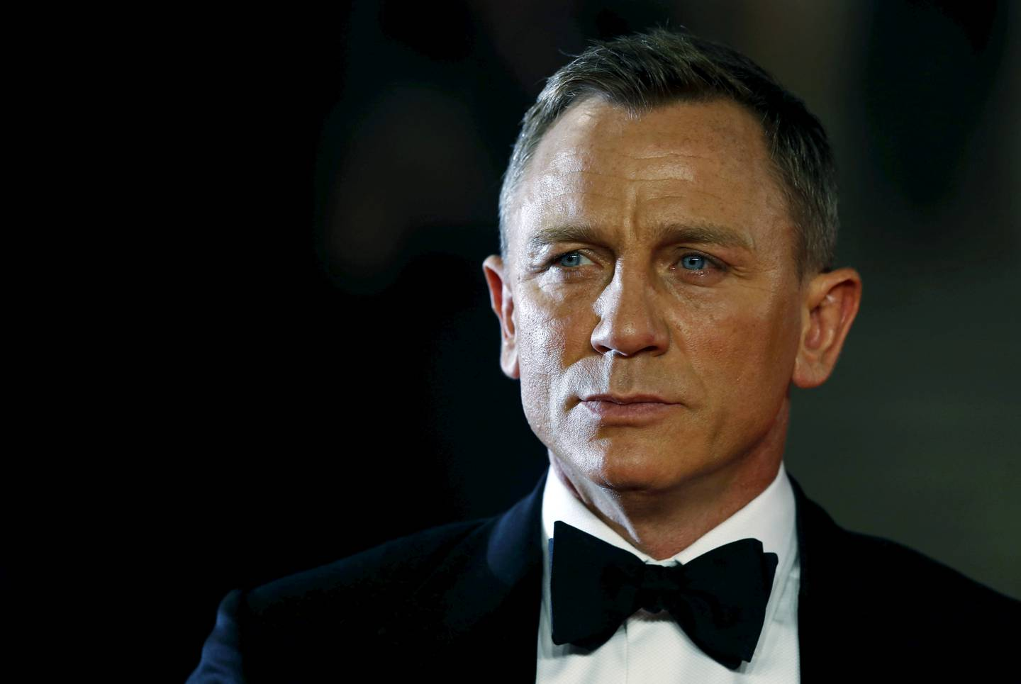 """FILE PHOTO: Daniel Craig poses for photographers as he attends the world premiere of the new James Bond 007 film """"Spectre"""" at the Royal Albert Hall in London, Britain, October 26, 2015. REUTERS/Luke MacGregor/File Photo"""