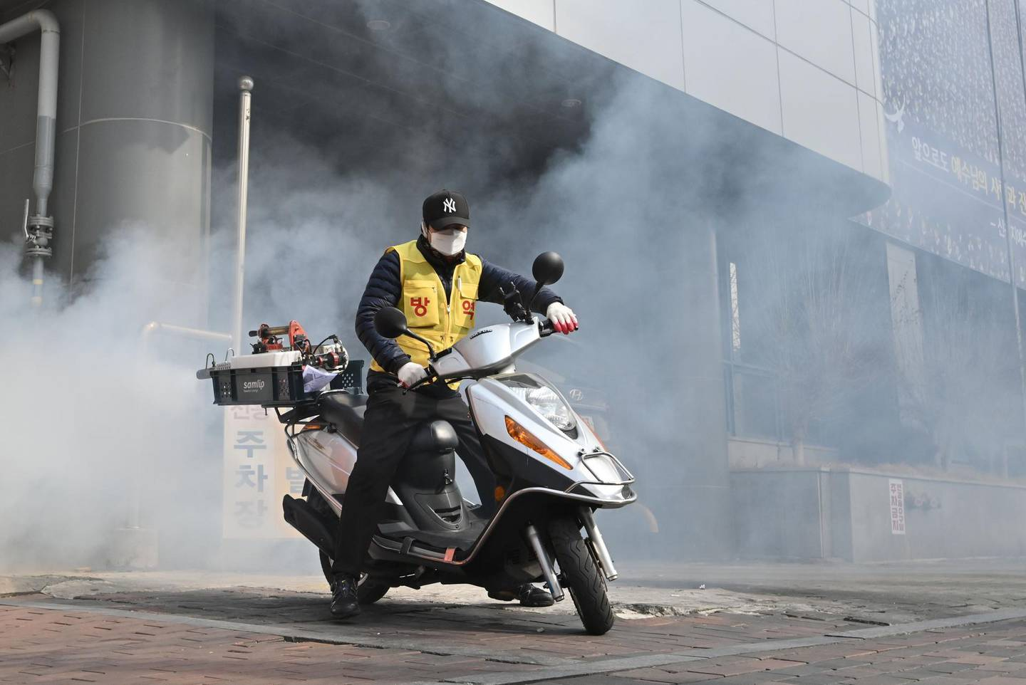 A South Korean health official sprays disinfectant in front of the Daegu branch of the Shincheonji Church of Jesus in the southeastern city of Daegu on February 21, 2020 as more than 80 members of Shincheonji have now been infected with the COVID-19 coronavirus. South Korea confirmed 52 more cases of novel coronavirus on February 21 as the number of infections linked to a religious sect in Daegu spiked, making it the worst-infected country outside China. / AFP / Jung Yeon-je