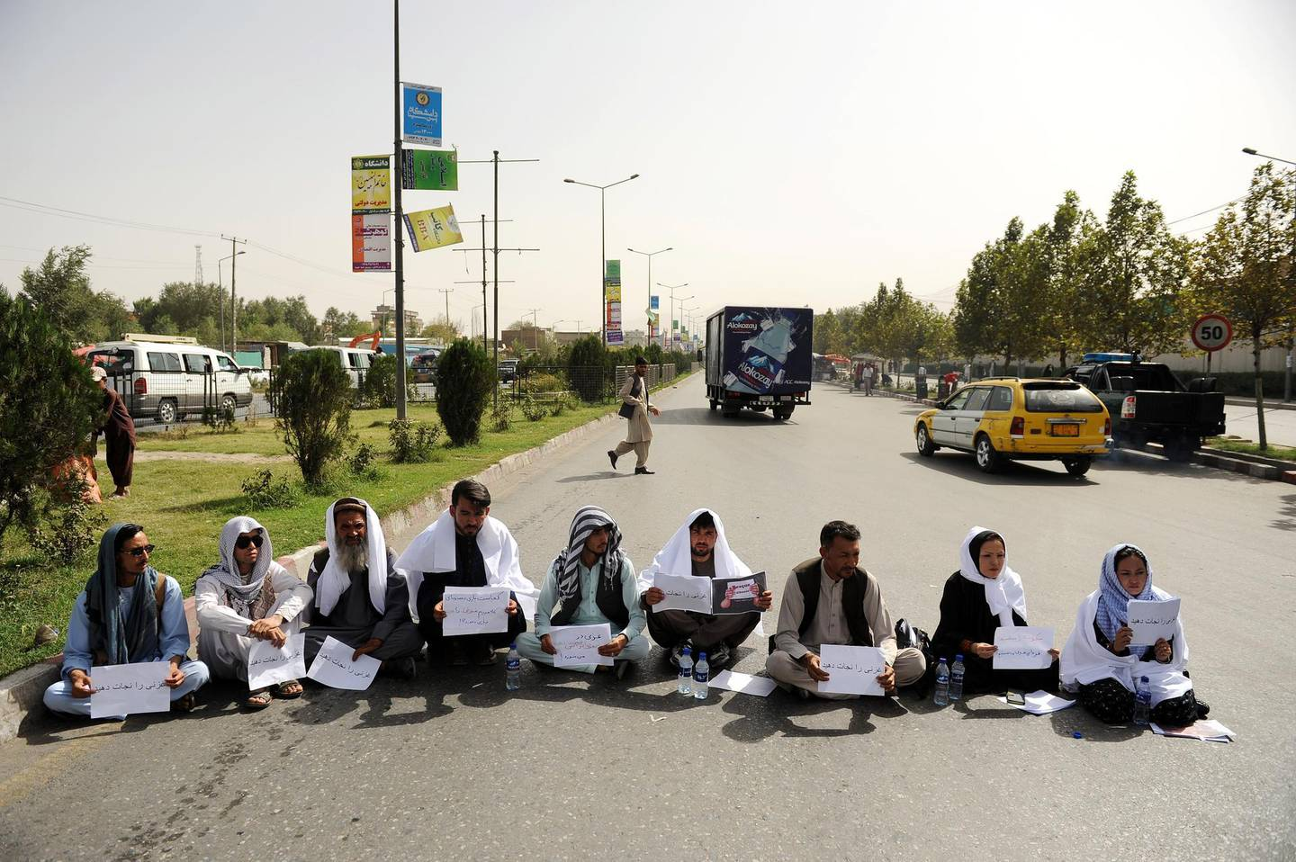 epa06947731 Two Afghan civil society women along with six other men wear gravecloths, hold placards written in farsi 'Rescue Ghazni Province' and block a busy road to pressure government for securing Ghazni province, in downtown Kabul, Afghanistan, 13 August 2018. The combat for the strategic city of Ghazni province has entered its fourth day, according to officials at least 135 people most of them police officers have been killed and 170 others are injured. Afghan special forces with US air force support have started a large operation to eliminate Taliban insurgents and take back the control of the city.  EPA/JAWAD JALALI