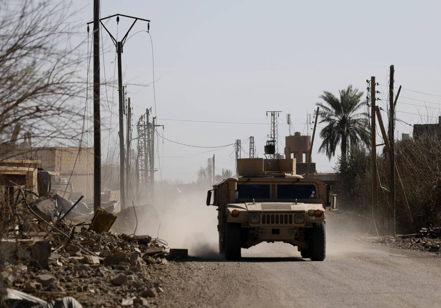 An armoured vehicle belonging to the Syrian Democratic Forces (SDF) drives in the front line village of Baghouz in the countryside of the eastern Syrian Deir Ezzor province, on the border with Iraq, on February 2, 2019.  The US-backed Syrian Democratic Forces halted their ground assault on IS's final shreds of territory last week as the jihadists increasingly used civilians as human shields to block the advance.  / AFP / DELIL SOULEIMAN