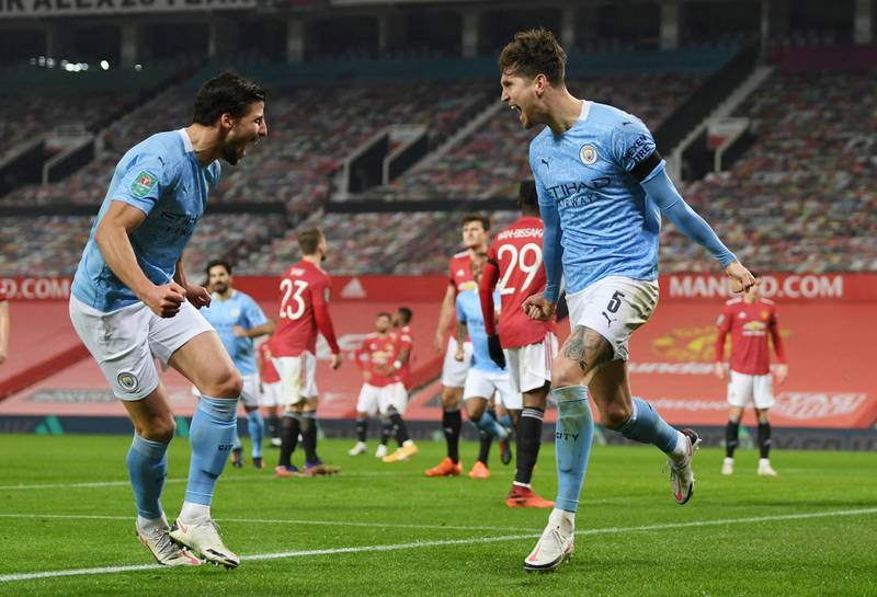 Soccer Football - Carabao Cup - Semi Final - Manchester United v Manchester City - Old Trafford, Manchester, Britain - January 6, 2021 Manchester City's John Stones celebrates scoring their first goal with teammates Pool via REUTERS/Shaun Botterill EDITORIAL USE ONLY. No use with unauthorized audio, video, data, fixture lists, club/league logos or 'live' services. Online in-match use limited to 75 images, no video emulation. No use in betting, games or single club /league/player publications.  Please contact your account representative for further details.     TPX IMAGES OF THE DAY
