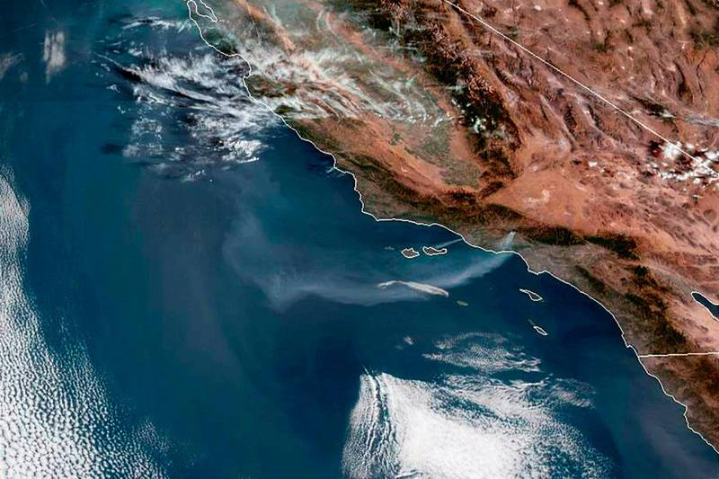 This satellite image from the National Oceanic and Atmospheric Administration (NOAA) shows a plume of smoke from the Saddleridge wildfire streaming out over the Pacific Ocean from the Los Angeles area of Southern California, center right, Friday morning, Oct. 11, 2019. (NOAA via AP)