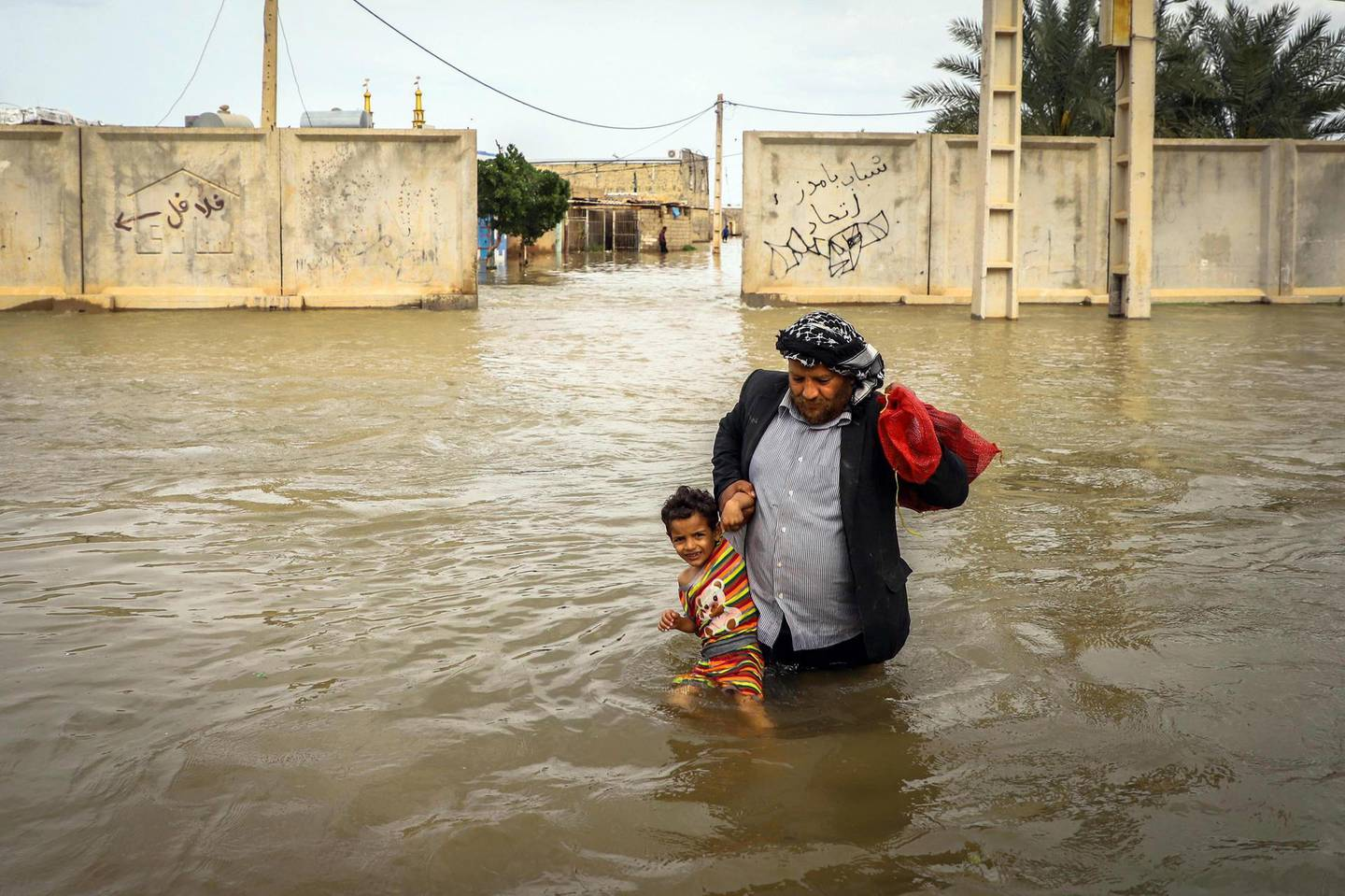epa07480225 An Iranian man carries his son in a flooded way in a village around the city of Ahvaz, Khuzestan province, Iran, 31 March 2019 (issued 02 April 2019).  At least 45 people have died in the past two weeks after heavy rains, with flooding affecting at least 23 of the country's 31 provinces.  EPA/SAEED SOROUSH