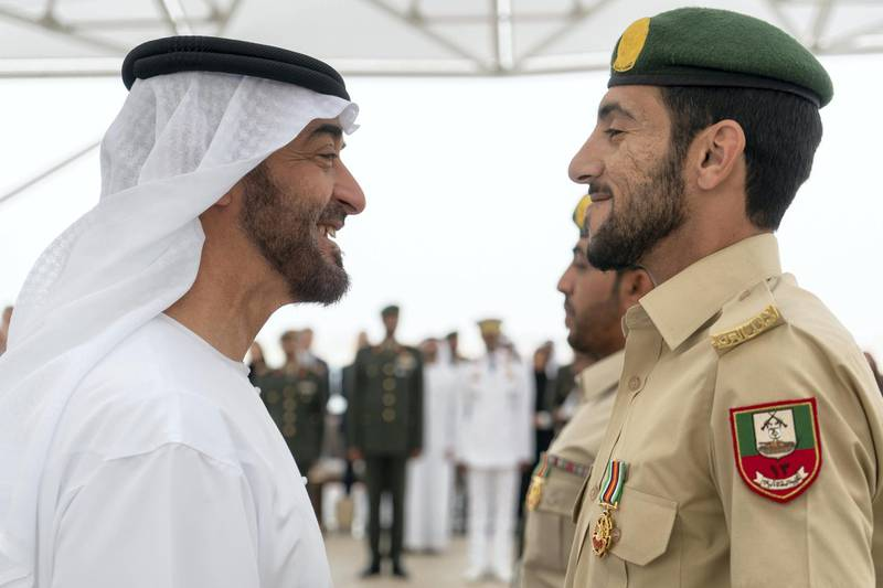 ABU DHABI, UNITED ARAB EMIRATES - April 23, 2018: HH Sheikh Mohamed bin Zayed Al Nahyan Crown Prince of Abu Dhabi Deputy Supreme Commander of the UAE Armed Forces (L), awards a member of the UAE Armed Forces with a Medal of Bravery for his service in Yemen, during a Sea Palace barza.  ( Rashed Al Mansoori / Crown Prince Court - Abu Dhabi )