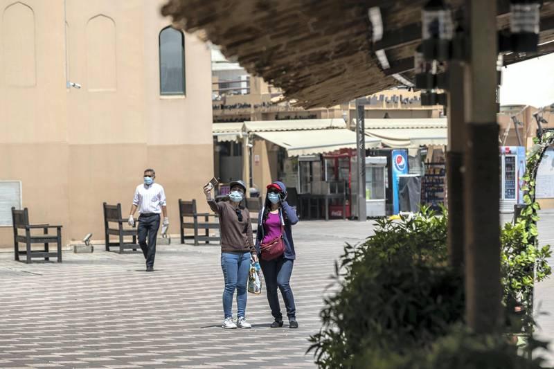 DUBAI, UNITED ARAB EMIRATES. 15 JUNE 2020. STANDALONE. Bur Dubai life during COVID-19.  Two woman take a selfie while walking along the Creek. (Photo: Antonie Robertson/The National) Journalist: None. Section: National.