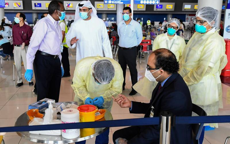 Health workers test an Indian national at the Dubai International Airport before leaving the Gulf Emirate on a flight back to his country, on May 7, 2020, amid the novel coronavirus pandemic crisis.  The first wave of a massive exercise to bring home hundreds of thousands of Indians stuck abroad was under way today, with two flights preparing to leave from the United Arab Emirates. India banned all incoming international flights in late March as it imposed one of the world's strictest virus lockdowns, leaving vast numbers of workers and students stranded.           / AFP / Karim SAHIB