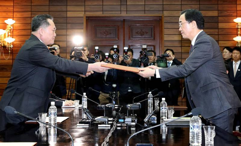 South Korean Unification Minister Cho Myoung-gyon exchanges documents with his North Korean counterpart Ri Son Gwon during their meeting at the truce village of Panmunjom, North Korea March 29, 2018. Korea Pool/Yonhap via REUTERS  ATTENTION EDITORS - THIS IMAGE HAS BEEN SUPPLIED BY A THIRD PARTY. SOUTH KOREA OUT. NO RESALES. NO ARCHIVE.