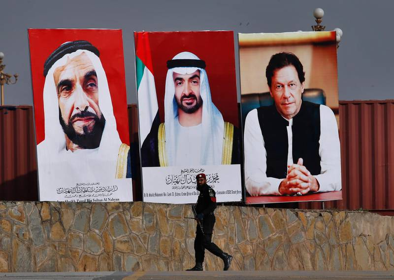 A police commando walks past the huge billboards showing the portraits of Abu Dhabi's Crown Prince, Sheikh Mohammed bin Zayed Al Nahyan, center, former President of the United Arab Emirates Sheikh Zayed bin Sultan Al Nahyan, left, and Pakistani Prime Minister Imran Khan to welcome crown prince to Islamabad, Pakistan, Sunday, Jan. 6, 2019. Abu Dhabi's crown prince is in Islamabad on daylong trip to discuss bilateral, International and regional issues with Pakistani leadership. Prince likely to announce billions to help Pakistani economy stabilized during visit. (AP Photo/Anjum Naveed)