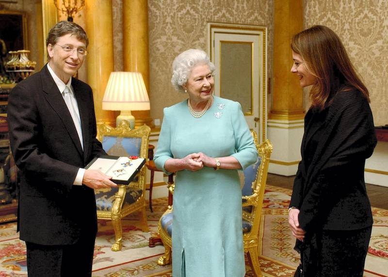 """Britain's Queen Elizabeth II presents Microsoft tycoon Bill Gates with his honorary knighthood at Buckingham Palace, London, Wednesday March 2, 2005 watched by his wife Melinda. Gates, one of the richest men in the world, cannot use the title """"Sir"""" as he is not a British citizen. He received the KBE insignia, in recognition of his charitable donations in Commonwealth countries.      AFP PHOTO/CHRIS YOUNG/WPA POOL (Photo by CHRIS YOUNG / POOL / AFP)"""