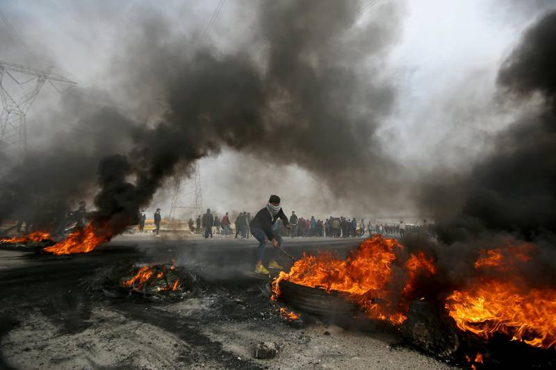 An Iraqi demonstrator moves burning tires during anti-government protests in Basra, Iraq, December 20, 2020. REUTERS/Essam al-Sudani