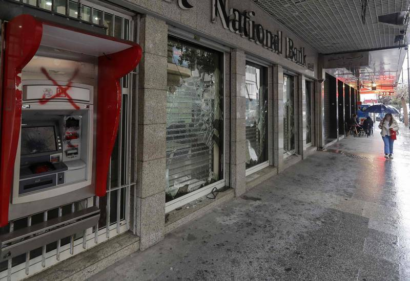A woman walks past a bank, with windows damaged by anti-government protesters, in the capital Beirut on March 6, 2020. Lebanon's central bank today ordered money changers to cap their exchange rate at no more than 30 percent above the official peg to contain the pound's devaluation on the parallel market. Debt-ridden Lebanon is facing its most serious economic crisis since the end of its 1975-1990 civil war.  / AFP / JOSEPH EID