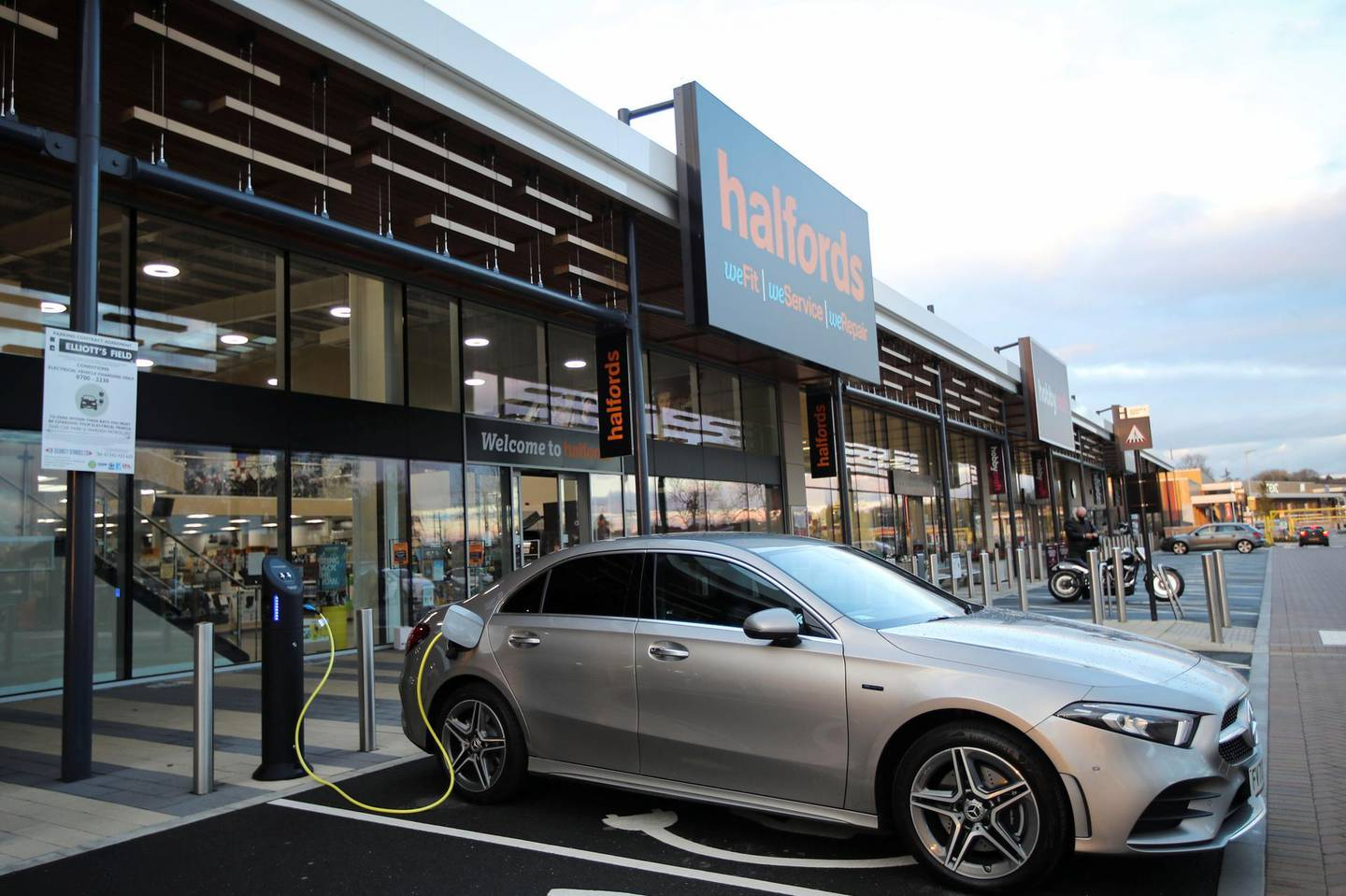 An electric car is seen at a charging point at Halfords in Rugby, Britain, November 19, 2020. REUTERS/Molly Darlington