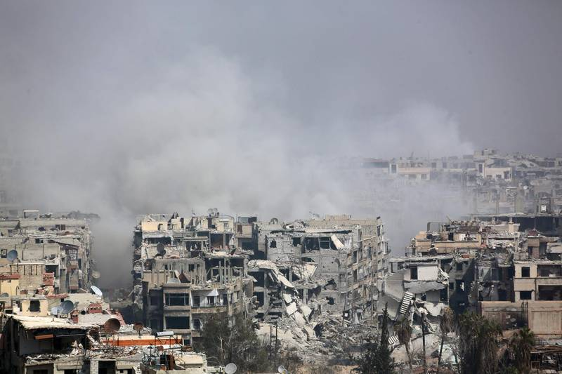 TOPSHOT - Smoke billows following Syrian government bombardment on the rebel-held besieged town of Harasta, in the Eastern Ghouta region on the outskirts of Damascus on March 12, 2018.  Syrian regime forces cut off the largest town in Eastern Ghouta from the rest of the opposition enclave in a blow to beleaguered rebels defending their last bastion near Damascus. Government troops and allied militia have recaptured half of the besieged region in a blistering assault launched on February 18 that has left nearly 1,000 civilians dead and prompted global outcry. / AFP PHOTO / -