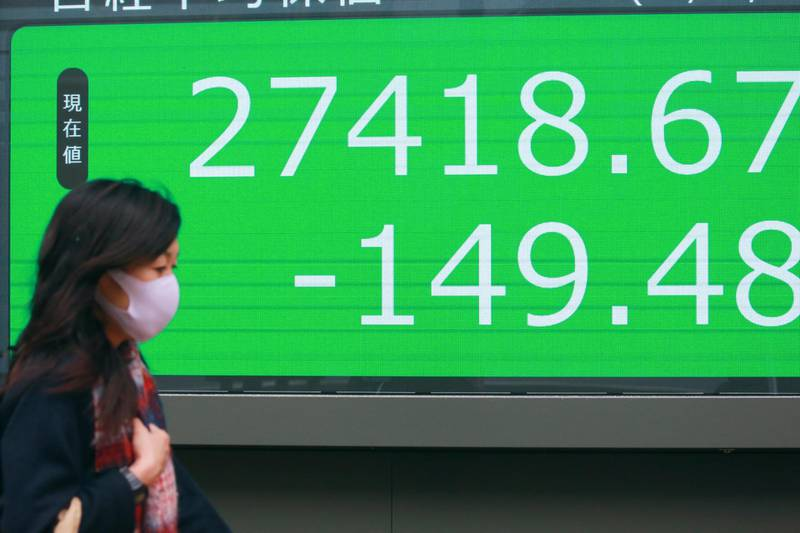 A woman walks by an electronic stock board of a securities firm in Tokyo, Wednesday, Dec. 30, 2020. Asian shares were mixed Wednesday after a lackluster day on Wall Street, as the boost from President Donald Trump's signing of the coronavirus relief package faded.(AP Photo/Koji Sasahara)