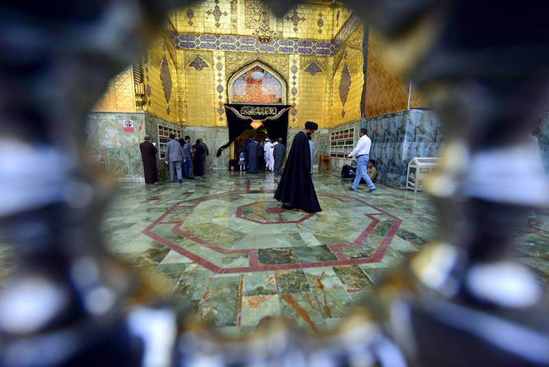 Visitors walk in a hall of the Imam Ali shrine, in the holy Iraqi central city of Najaf where the first case of novel coronavirus infection in the country was confirmed, on March 10, 2020. (Photo by Haidar HAMDANI / AFP)