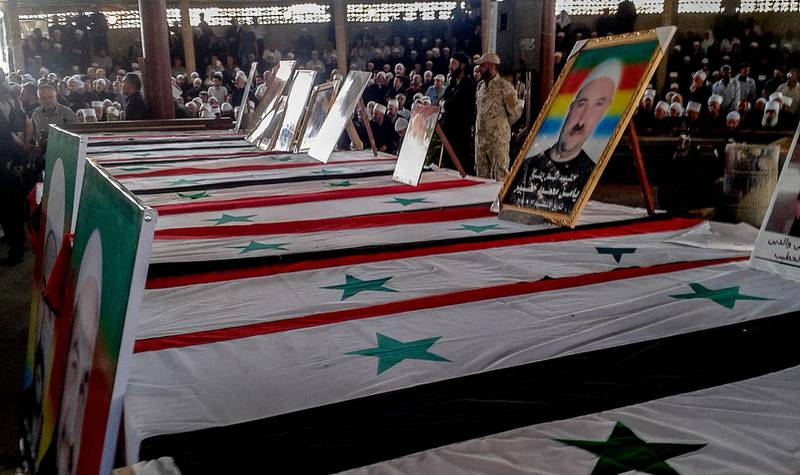 epa06911180 A handout photo made available by Syrian Arab news agency (SANA) shows Druze clerics and citizens sit next to the coffins during a massive popular funeral ceremony for the martyrs of the attacks that targeted the al-Sweida province, southern Syria, 26 July 2018. According to reports on 25 July 2018, 220 citizens were killed and others were injured in suicide bombing attacks at al-Sweida city synchronizing with Islamic State (IS) attacks on a number of villages in the eastern and northern countryside of the province.  EPA/SANA HANDOUT HANDOUT  HANDOUT EDITORIAL USE ONLY/NO SALES