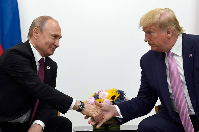 FILE - In this June 28, 2019, file photo, President Donald Trump, right, shakes hands with Russian President Vladimir Putin, left, during a bilateral meeting on the sidelines of the G-20 summit in Osaka, Japan. Intelligence officials say Russia is interfering with the 2020 election to try to help Trump get reelected, The New York Times reported Thursday, Feb. 20, 2020. (AP Photo/Susan Walsh, File)