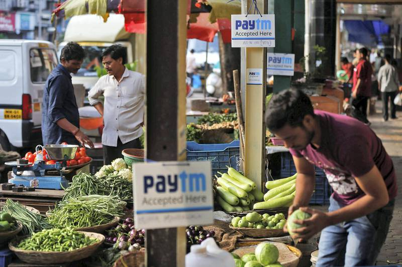Advertisement boards of Paytm, a digital wallet company, are seen placed at stalls of roadside vegetable vendors as they wait for customers in Mumbai, India, November 19, 2016. Picture taken November 19, 2016. REUTERS/Shailesh Andrade - RC125A6CB600