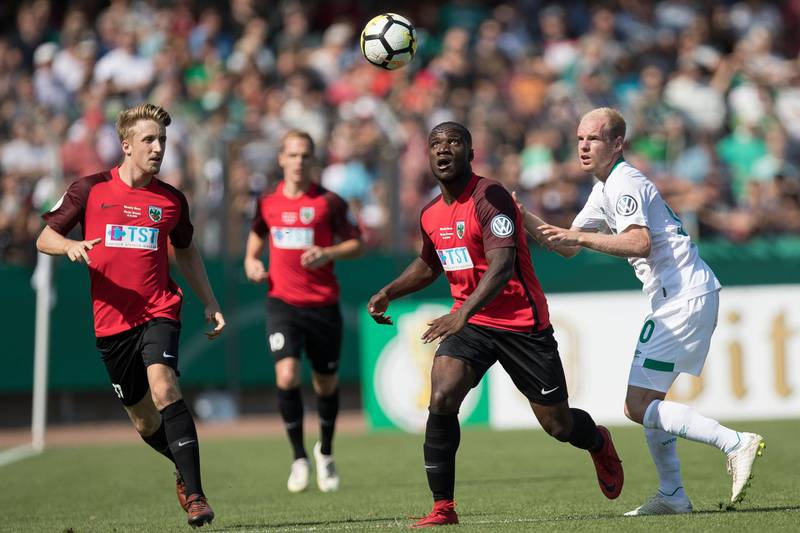 WORMS, GERMANY - AUGUST 18: Perric Afari of VfR Wormatia Worms and Davy Klaassen #30 of Werder Bremen battle for the ball during Wormatia Worms and Werder Bremen DFB Cup first round match on August 18, 2018 in Worms, Germany. (Photo by Maja Hitij/Bongarts/Getty Images)