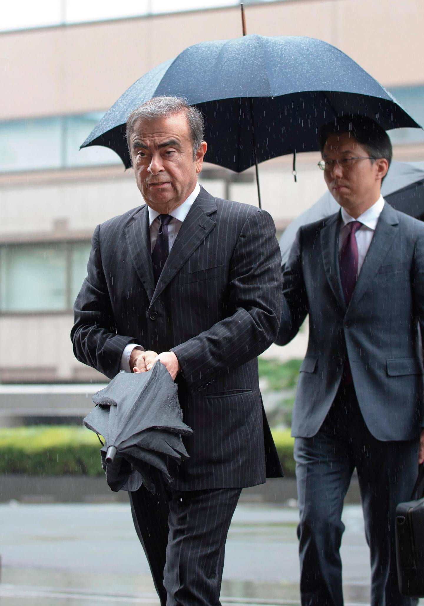 """(FILES) In this file photo taken on June 24, 2019 former Nissan Motor Chairman Carlos Ghosn (L) arrives for a pre-trial hearing at the Tokyo District Court in Tokyo. A year after Japan learned with horror that Carlos Ghosn had jumped bail to become the world's most famous fugitive, the fiasco and its repercussions continue to haunt the country. Ghosn was living in a monitored Tokyo apartment awaiting trial on financial misconduct charges when he casually boarded a train to Osaka in western Japan on December 29, 2019 with two accomplices. - TO GO WITH AFP FOCUS """"JAPAN-GHOSN-AUTOMOBILE-LEBANON-NISSAN-RENAULT"""" BY ETIENNE BALMER   / AFP / Kazuhiro NOGI / TO GO WITH AFP FOCUS """"JAPAN-GHOSN-AUTOMOBILE-LEBANON-NISSAN-RENAULT"""" BY ETIENNE BALMER"""