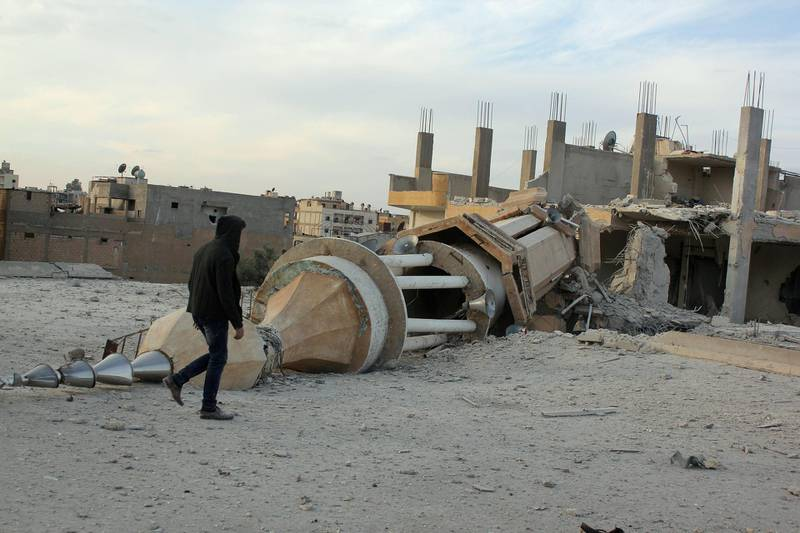 A Syrian man walks past a minaret destroyed following an alleged air strikes by Syrian government forces in the Islamic State (IS) group controlled Syrian city of Raqa, on November 25, 2014. A string of Syrian regime air strikes on the Islamic State group's self-proclaimed capital Raqa killed at least 63 people, more than half of them civilians, a monitor said. The air strikes were the deadliest by President Bashar al-Assad's air force against Raqa since the Sunni extremist IS seized control of the city last year.  AFP PHOTO/RMC/STR (Photo by STR / Raqa Media Center / AFP)