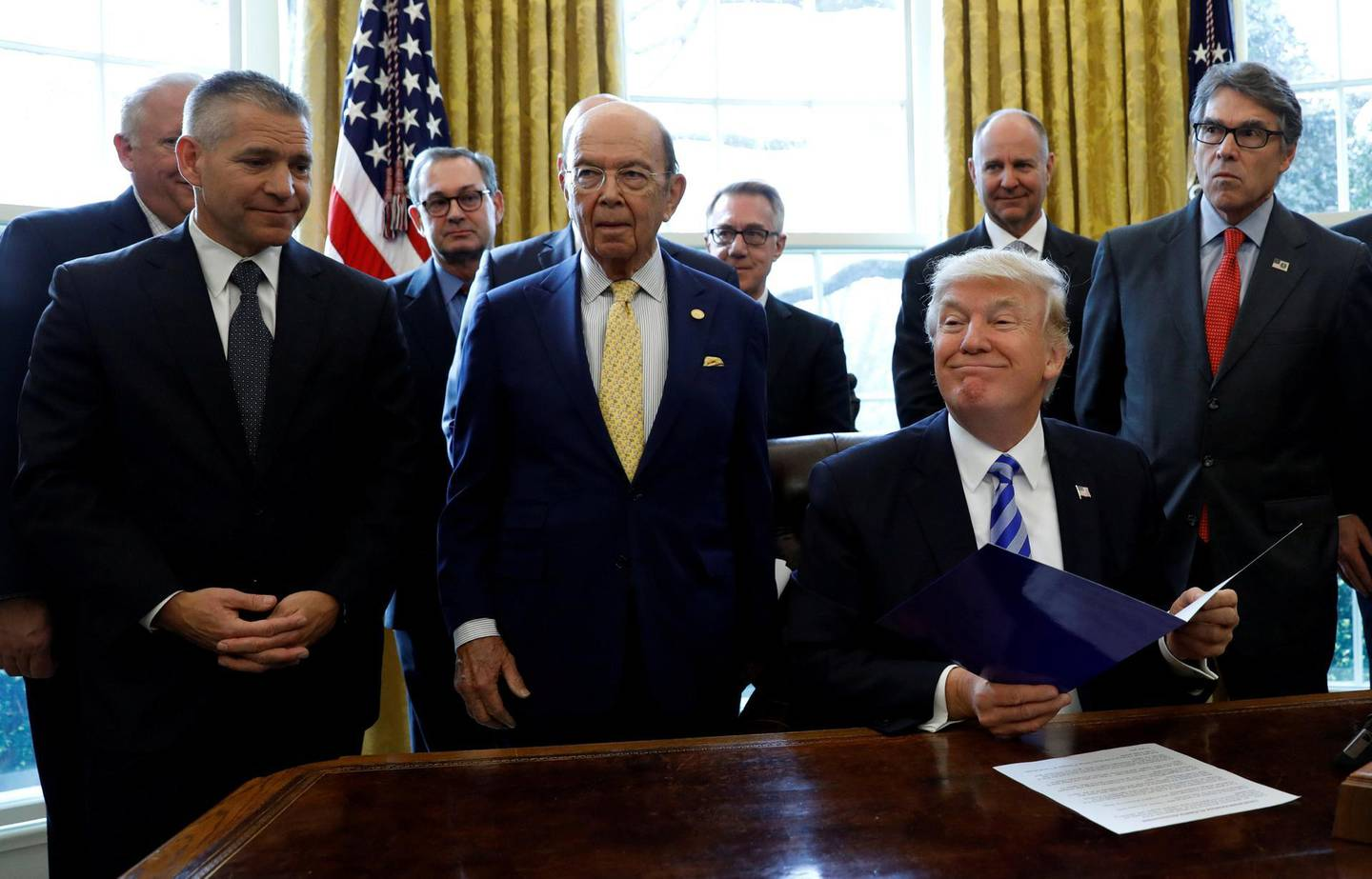 FILE PHOTO: U.S. President Donald Trump smiles after announcing a permit for TransCanada Corp's Keystone XL oil pipeline while TransCanada Chief Executive Officer Russell Girling (L), U.S. Commerce Secretary Wilbur Ross (C) and Energy Secretary Rick Perry (R) stand beside him in the Oval Office of the White House in Washington, U.S., March 24, 2017. REUTERS/Kevin Lamarque/File Photo