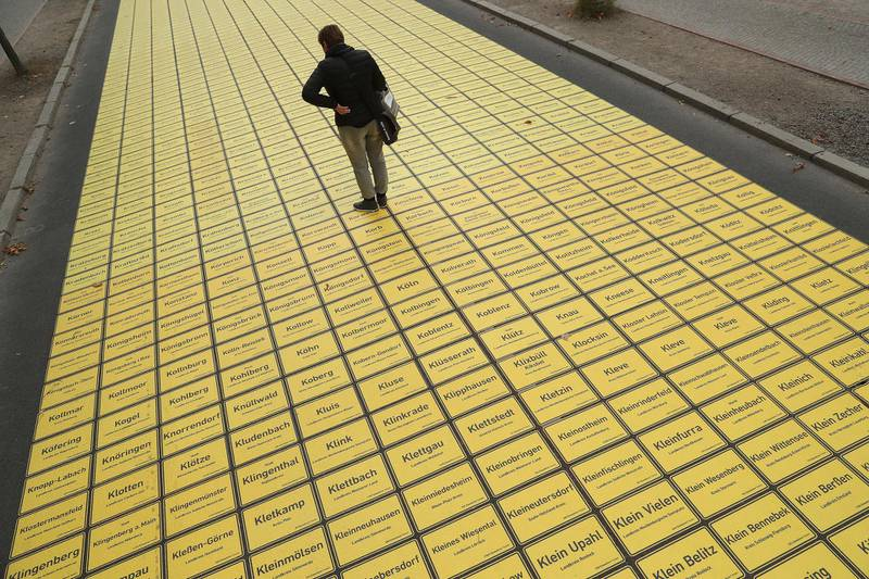 BERLIN, GERMANY - OCTOBER 01:  A man stops to look at city limits signs that form a walkway in the city center as part of celebrations to mark German Unity Day scheduled for Wednesday on October 1, 2018 in Berlin, Germany. All of Germany's 11,400 villages, towns and cities are represented in the winding path of signs through Berlin's government quarter. Germany will celebrate Unity Day (Tag der Deutschen Einheit) on October 3 with the the main event to take place this year in Berlin. (Photo by Sean Gallup/Getty Images)