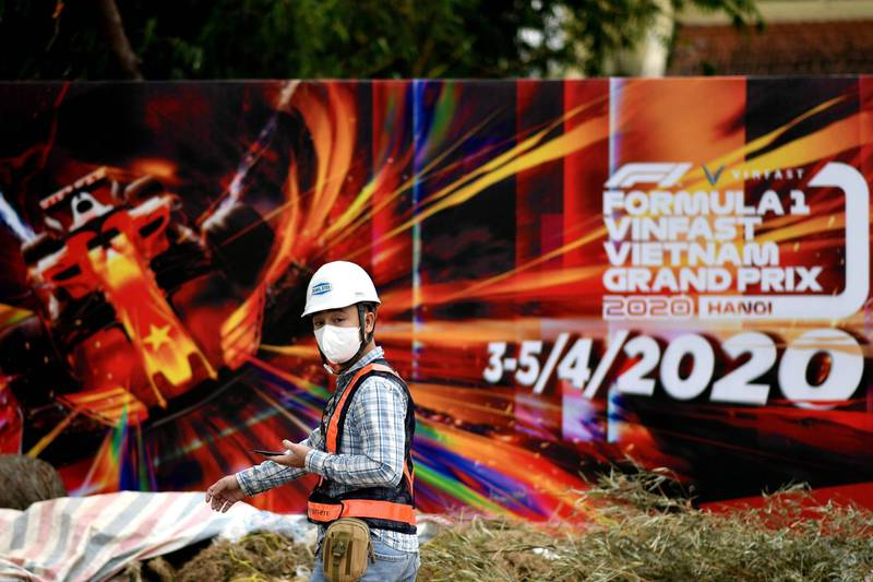 (FILES) In this file photo taken on March 10, 2020, a worker, wearing a facemask amid concerns of the Covid-19 coronavirus outbreak, walks past hoarding at the Formula One Vietnam Grand Prix race track site in Hanoi. Vietnam's first Formula One Grand Prix has been dropped from the 2021 calendar, according to a November 10, 2020 report on the BBC. The move had been triggered on the arrest on corruption charges of a key official responsible for the race in Hanoi, it added. / AFP / Manan VATSYAYANA