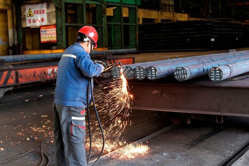 """A worker cuts steel at a factory in Zouping in China's eastern Shandong province on April 9, 2018.  China said on April 6 it is ready to pay """"any cost"""" in a trade war after US President Donald Trump threatened an additional 100 billion USD in tit-for-tat tariffs on Beijing. / AFP PHOTO / - / China OUT"""
