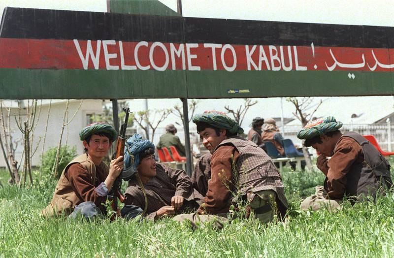 """Afghan Uzbek militiamen belonging to safe-styled General Abdul Rashid Dostam, an Uzbek warlord, relax on a patch grass beneath a sign reading """"Welcome to Kabul"""" 01 May 1992 at the VIP section of the airport in the Afghan capital. Words on the sign are drawn across the colours of the Afghan national flag flown under the late Soviet-backed communist regime. Dostam, in 1992 mutinied against to government of Mohammed Najibullah allying with Ahmed Shah Massoud. Together, they captured Kabul. AFP PHOTO DOUGLAS E. CURRAN (Photo by DOUGLAS E. CURRAN / AFP)"""