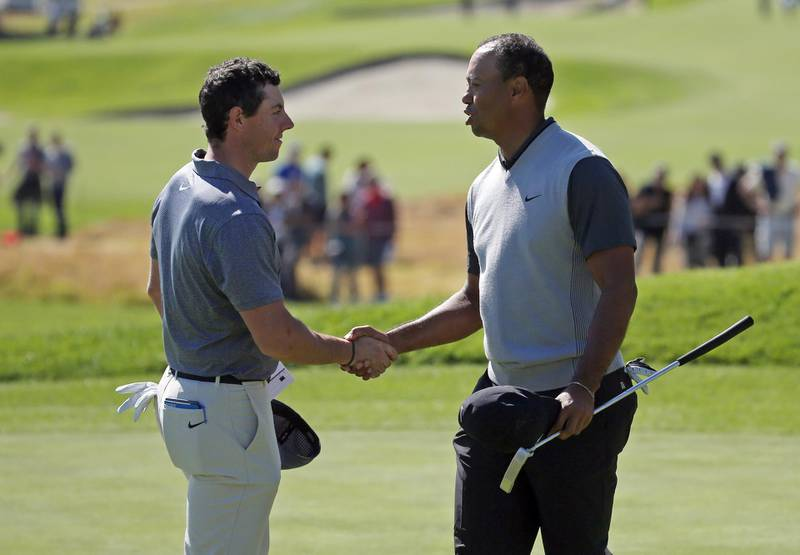 Tiger Woods, right, and Rory McIlroy shake hands at the end of their first round of the Genesis Open golf tournament at Riviera Country Club in the Pacific Palisades neighborhood of Los Angeles Thursday, Feb. 15, 2018. (AP Photo/Reed Saxon)