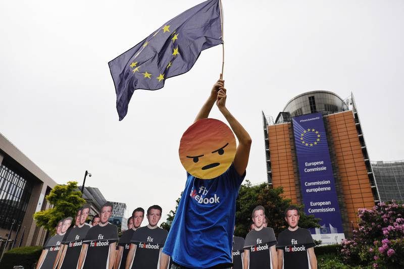 A protester waves a European Union (EU) flag beside cutouts of Facebook Inc. Chief Executive Officer Mark Zuckerberg during a protest outside the Berlaymont building ahead of his testimony to the European Union (EU) parliament in Brussels, Belgium, on Tuesday, May 22, 2018. Zuckerberg will tout the companys investment in Europe and again take responsibility for privacy failures, according to testimony prepared for an appearance Tuesday in front of the regions parliament. Photographer: Dario Pigantelli/Bloomberg