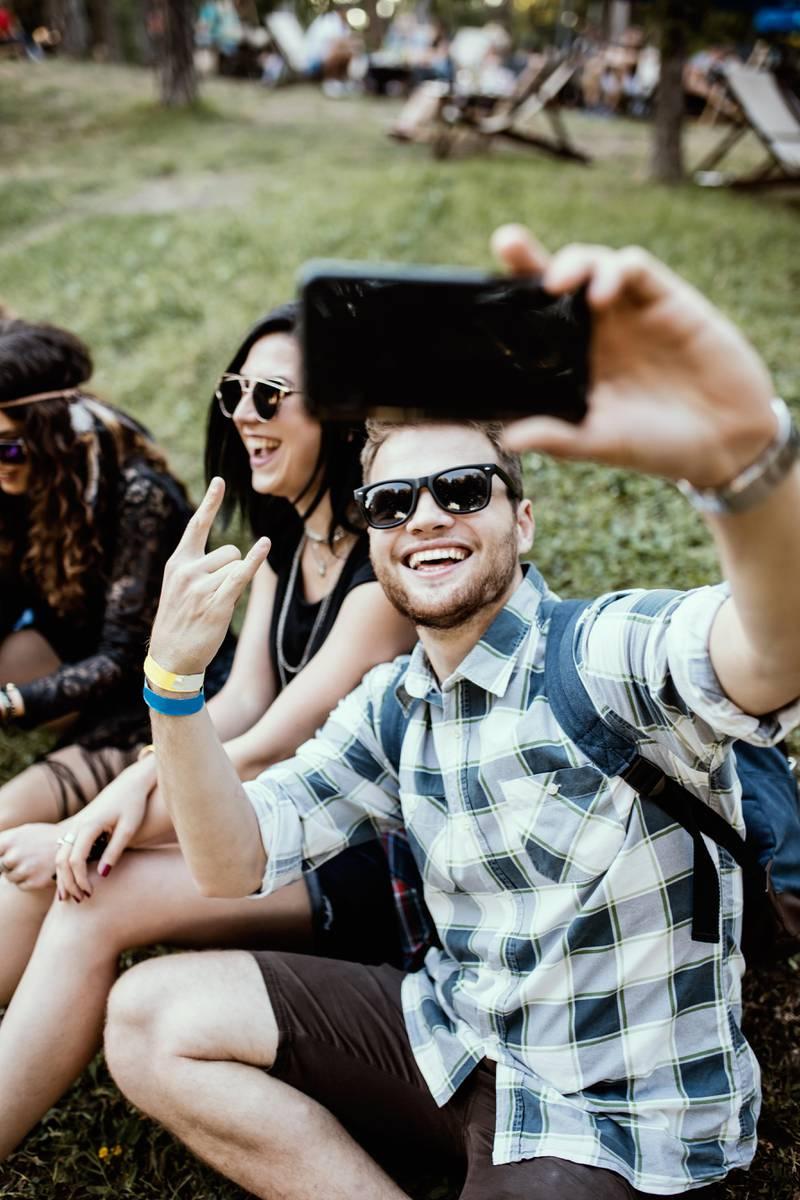 Friends sitting on the meadow, cute guy taking selfie
