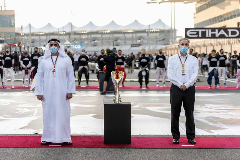YAS MARINA, ABU DHABI, UNITED ARAB EMIRATES - December 13, 2020: HH Lt General Sheikh Saif bin Zayed Al Nahyan, UAE Deputy Prime Minister and Minister of Interior (L), and Chase Carey, Formula 1 Chairman and CEO (R), stand for the national anthem prior to the final race of the 2020 Formula 1 Etihad Airways Abu Dhabi Grand Prix, at Yas Marina Circuit.   ( Hamad Al Kaabi / Ministry of Presidential Affairs ) ---