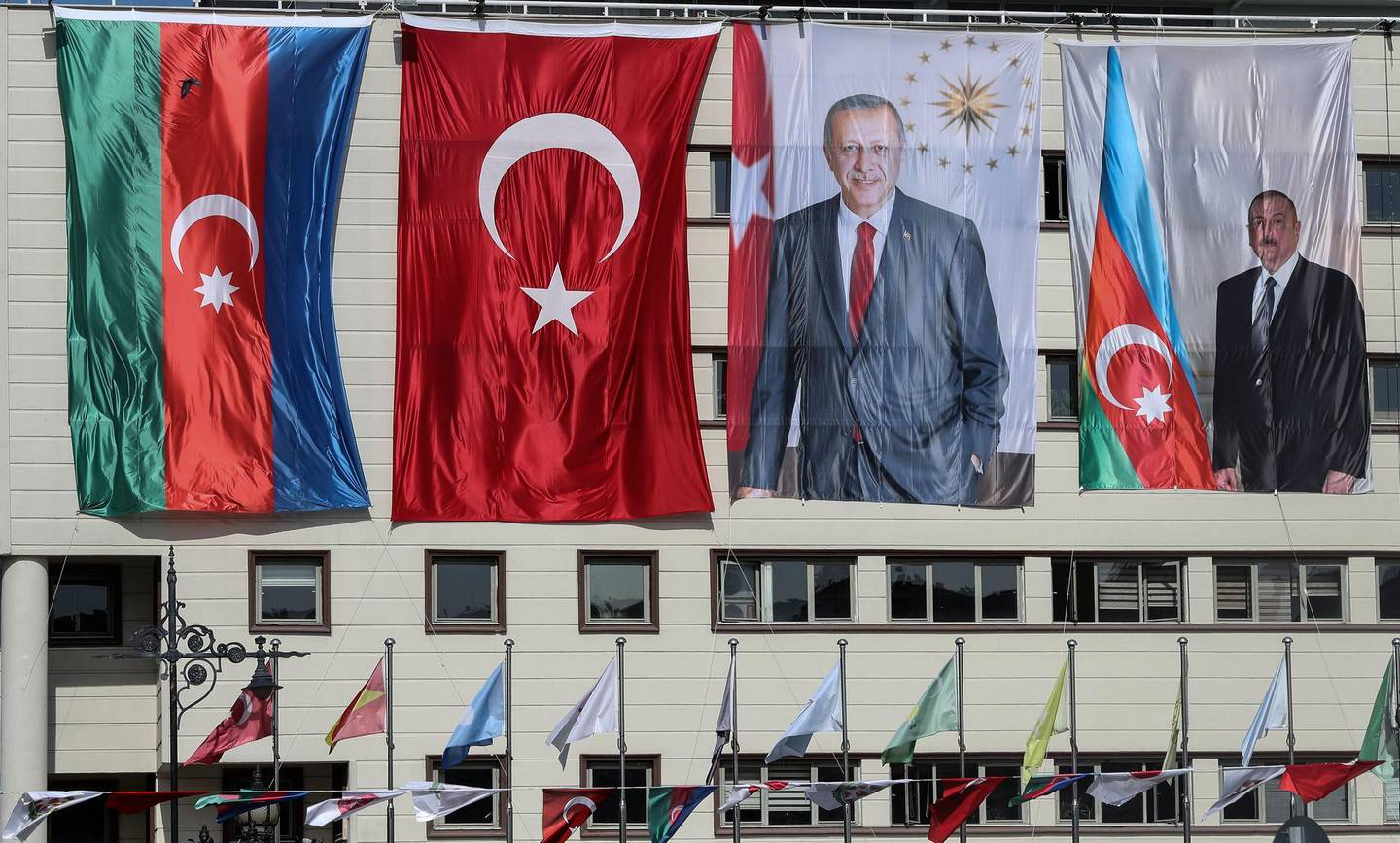 The national flags of Azerbaijan (L) and Turkey, and portraits of Turkish President Recep Tayyip Erdogan and Azerbaijani President Ilham Aliyev (R) hang side-by-side on the  mayoral building in the Kecioren district of Ankara on October 21, 2020.    The origins of a flareup in fighting over Nagorno-Karabakh that has now killed hundreds and threatens to involve regional powers Turkey and Russia are hotly contested and difficult to independently verify. Both sides accuse the other of striking first on September 27 over the ethnic Armenian region of Azerbaijan. / AFP / Adem ALTAN