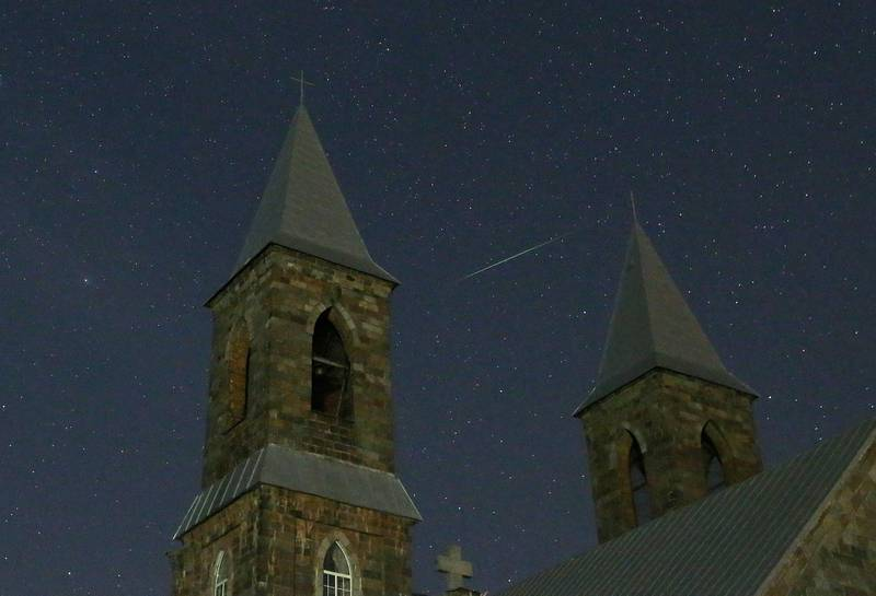 epa06141525 A meteor of the Perseids meteor shower burns up in the atmosphere behind a Catholic church near the village of Rubezhevichi, some 50 km from Minsk, Belarus, late 12 August 2017. The Perseid meteor shower occurs every year in August when the Earth passes through debris and dust of the Swift-Tuttle comet.  EPA/TATYANA ZENKOVICH