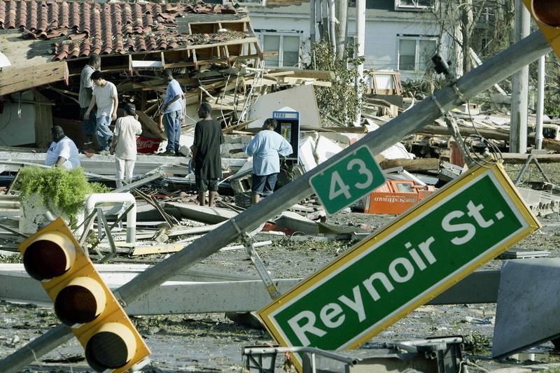 Residents inspect damage left by Hurricane Katrina 30 August 2005, in Biloxi, Mississippi. At least 80 people were feared dead along the coast of the southern state of Mississippi, where glitzy casinos, plush homes and shrimp fishing businesses lay in ruins, after a storm surge up to 30 feet (10 metres) high crashed ashore on Monday. Helpless authorities in New Orleans meanwhile watched as surging floodwaters gushed through a 200 feet (600 meter) hole in the 17th Street Canal defences, indundating a low-lying city already 80 percent under water. AFP PHOTO/Robert SULLIVAN (Photo by ROBERT SULLIVAN / AFP)
