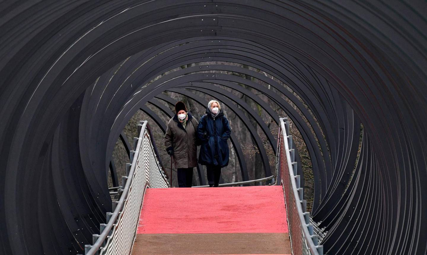 People wear protective face masks due to the coronavirus pandemic, as they walk over a bridge during the lockdown in Oberhausen, Germany, Monday, Jan. 11, 2021. (AP Photo/Martin Meissner)
