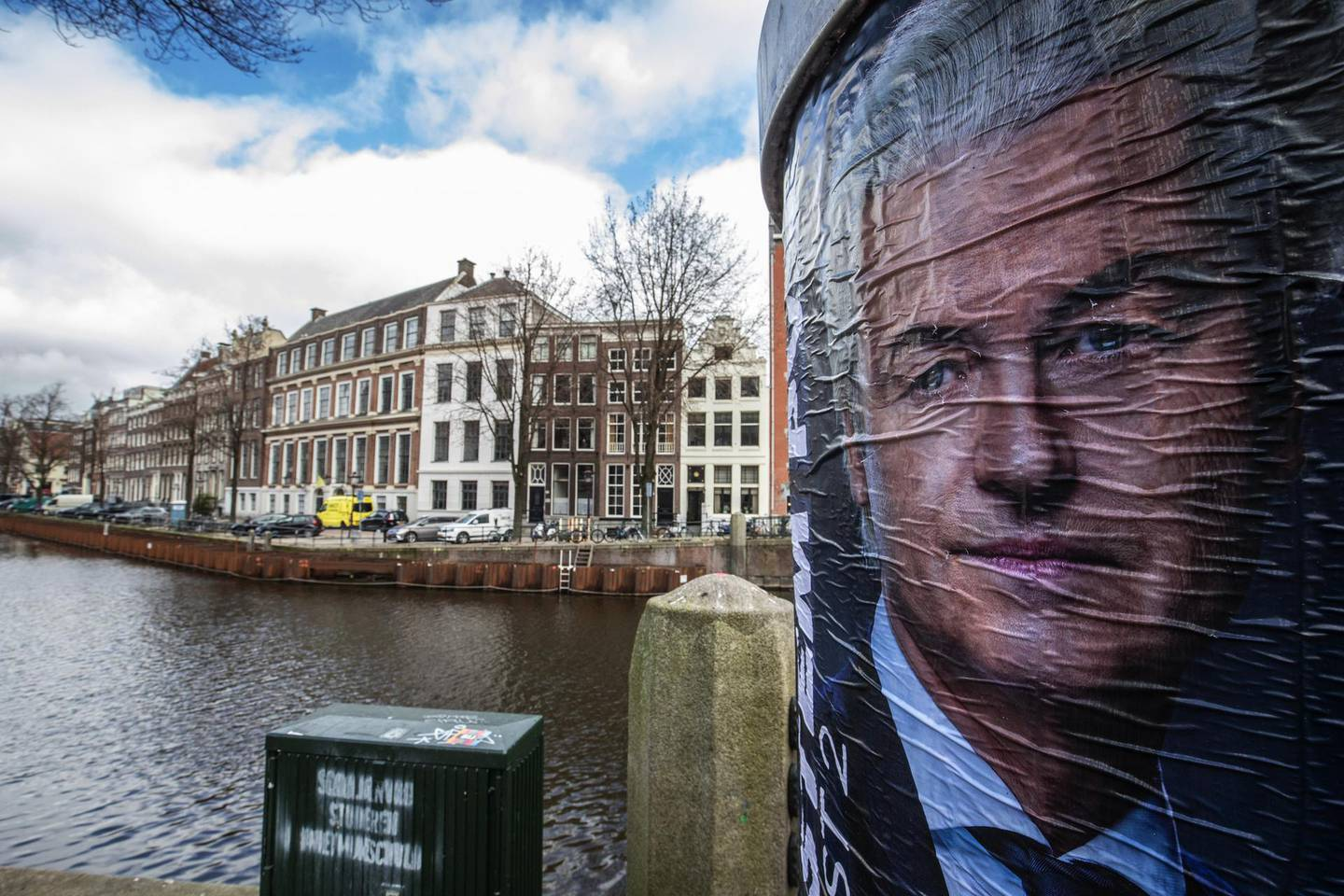 An election campaign poster featuring Geert Wilders, leader of the Party for Freedom (PVV), beside a canal in Amsterdam, Netherlands, on Wednesday, March 17, 2021. Dutch voters go to the polls on Wednesday with Prime MinisterMark Ruttelooking to clinch a fourth consecutive term, a result that would set himup tobecome the country's longest-serving premier and a senior statesman in Europe. Photographer: Peter Boer/Bloomberg