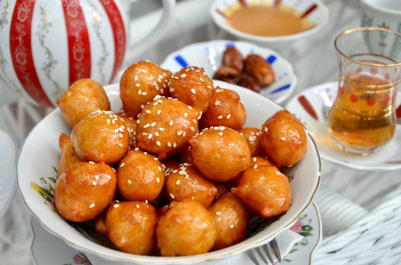 2CCRGTG Traditional oriental dessert speciality Legematt (Luqaimat), fried dough balls in a porcelain bowl, blurred dates and a cup of tea behind. Image shot 05/2019. Exact date unknown.